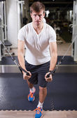 Young man working out in gym pecs exercise — ストック写真