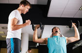 Young man motivating gym buddy during shoulder exercise — Stock Photo