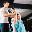 Personal trainer working with his client in gym helping him with — Stock Photo