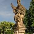Saint Augustine statue holding a burning heart in hand, Charles bridge in Prague - Stock Photo