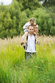 Happy father carrying daughter on his neck — Stock Photo
