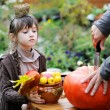 Little girl watching the carvin of pumpkin — Stock Photo
