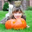 Little girl lying on a grass with big pumpkin - Stock Photo