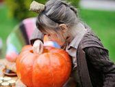 маленькая девочка, заглянув внутрь большой тыквы — Стоковое фото