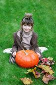 Kleines mädchen sitzt auf gras mit großen kürbis — Stockfoto