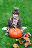 Little girl sitting on grass with big pumpkin — Stock Photo