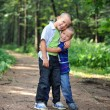 Stock Photo: Brothers hugging each other outdoors
