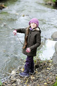 Portrait of little girl in pink hat by a river — Stock Photo