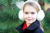 Portrait of little girl in white earmuffs — Stock Photo
