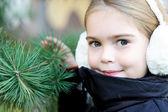 Portrait of little girl in white earmuffs — Stock Photo