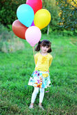 Outdoor portrait of little girl with baloons — Stock Photo