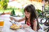 Little girl having breakfast outdoors — Stock Photo