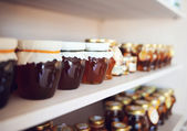 Shelf with home-made honey and jam — Stock Photo