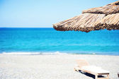 Tranquil sea shore with parasol and sunbed — Stok fotoğraf