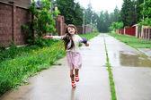 Elegant child girl walking on a rainy day — Stock Photo