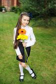 νεαρή κοπέλα στη σχολική στολή ποζάρει με λουλούδια — 图库照片