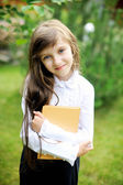 Young girl in school uniform holding a book — Stock Photo