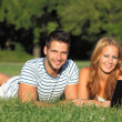 Young couple with a notebook in the park — Stock Photo