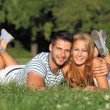 Cute young couple lying in the grass — Stock Photo #12189283