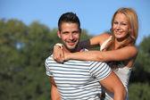 Mladé ženy, objal její přítel v parku — Stock fotografie