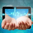 Electrocardiogram on hand pushing out of tablet-pc — Stock Photo
