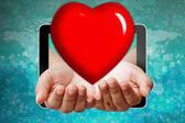 Heart on hand pushing out of tablet-pc — Stock Photo