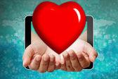Serce na dłoni przesuwając z komputera typu tablet — Zdjęcie stockowe