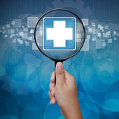 First Aid icon in Magnifying glass on blue background — Stock Photo