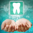 Stock Photo: Tooth Symbol on hand,medical background