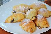Croissant fresco e saboroso prato branco — Fotografia Stock