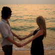 Lover Holding hands together on the beach at sunset — Stock Photo