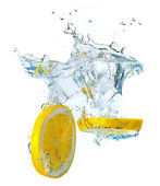 Lemon slices and ice cubes splashing water — Stock Photo