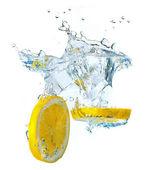 Lemon slices and ice cubes splashing water — Stock Photo