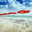 Red umbrellas on beach — Stock Photo #25934845