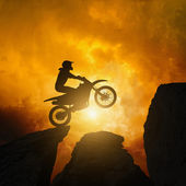 Motorcircle rider in rocks — Stock Photo