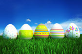 Happy Easter, colored eggs in a grass field — Stock Photo