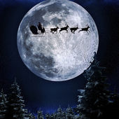 Santa flying in his sleigh against a full moon background — Stock Photo