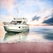 Yacht anchored on the beach with couples foot prints in the sand — Stock Photo