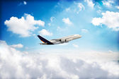 Jet airplane peaking through the clouds — Stock Photo