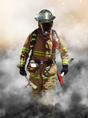 A firefighter pierces through a wall of smoke searching for survivors. — Stock Photo