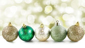 Christmas balls in a row with light and festive bokeh background — Stock Photo