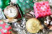 Old clock almost 12 on dial with tree branch and ornaments — Stock Photo