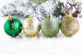 Christmas balls with snowflakes falling and tree in background — Stock Photo