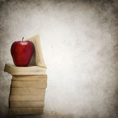 Grunge background with stack of books and red apple — Stock Photo