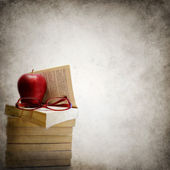 Grunge background with stack of books, apple and eyeglasses — Stock Photo