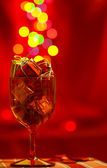 Festive red background with glass, present boxes and bokeh — Stock Photo