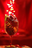 Festive background with glass, present boxes and hearts bokeh — Stock Photo