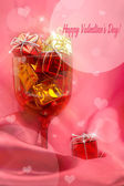 Pink festive background with glass, present boxes and hearts — Stock Photo
