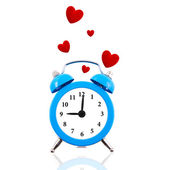 Alarm clock with floating red hearts isolated on white — Stock Photo