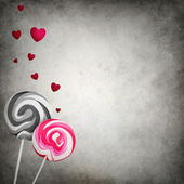 Unmatched lollipops with floating hearts on grunge background — Photo